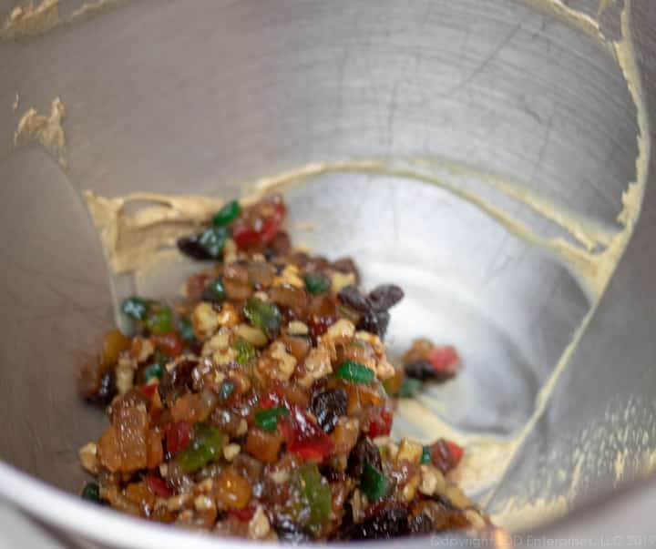 mixed fruit in batter in a mixing bowl for fruitcake