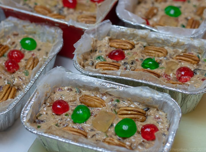 filled fruitcake pans with fruit and nut garnish