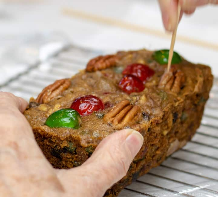 a hand poking the top of the fruitcake on a cooling rack with a toothpic