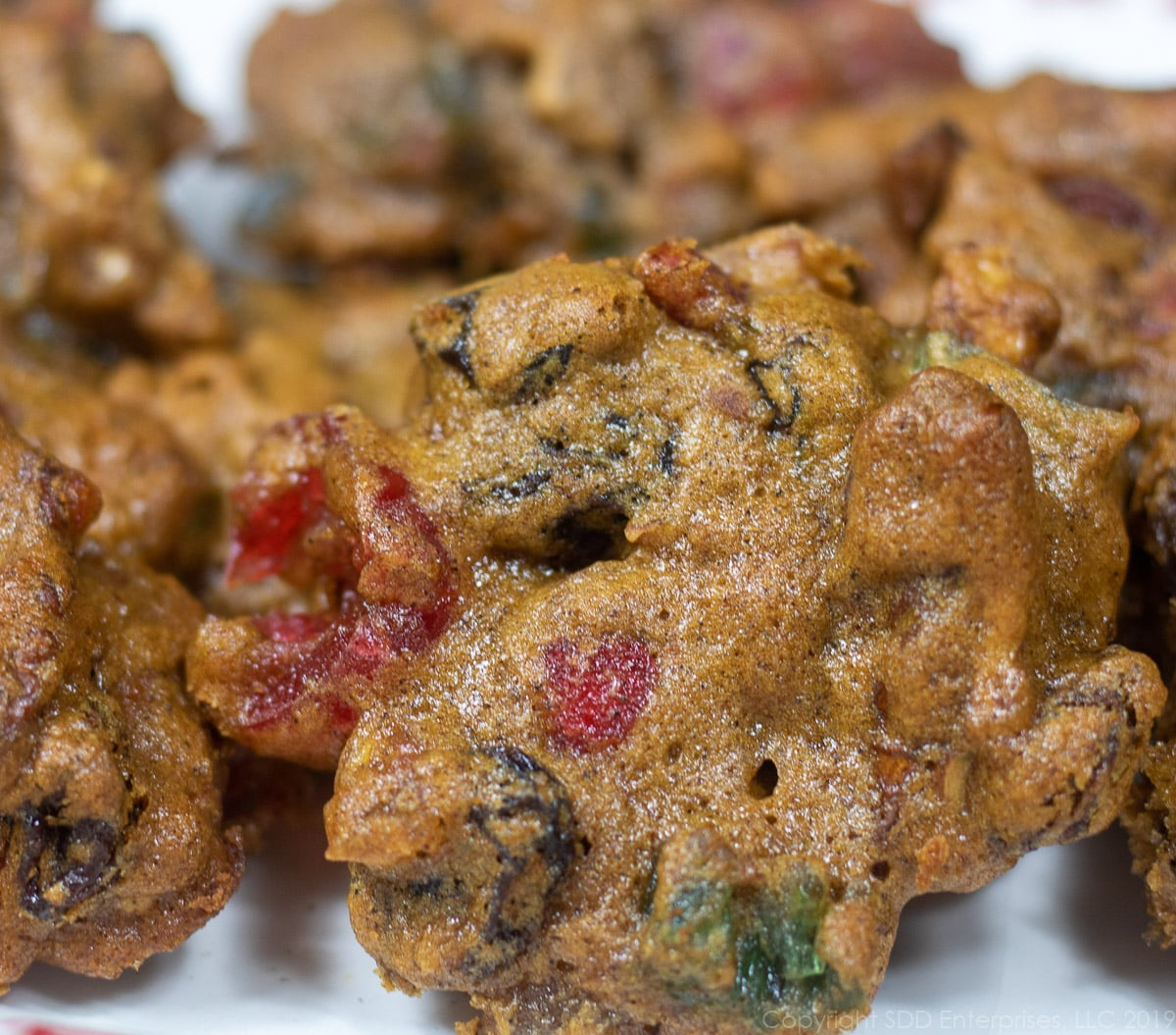 several fruitcake cookies, or Christmas Lizzies on a white plate