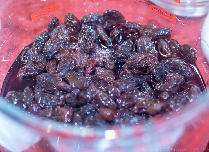 dark raisins marinading in cherry randy in a measuring cup