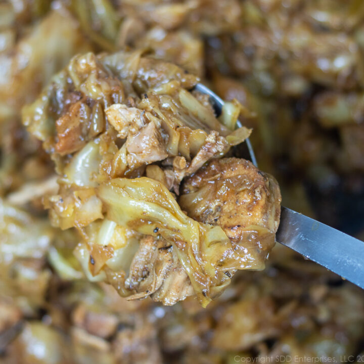 smothered cabbage with pork in a spoon over a pot of smothered cabbage