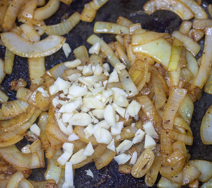 chopped garlic and sliced onions frying in dutch oven for smothered cabbage