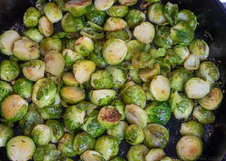 sauteed brussels sprouts with herbs in a cast iron pan