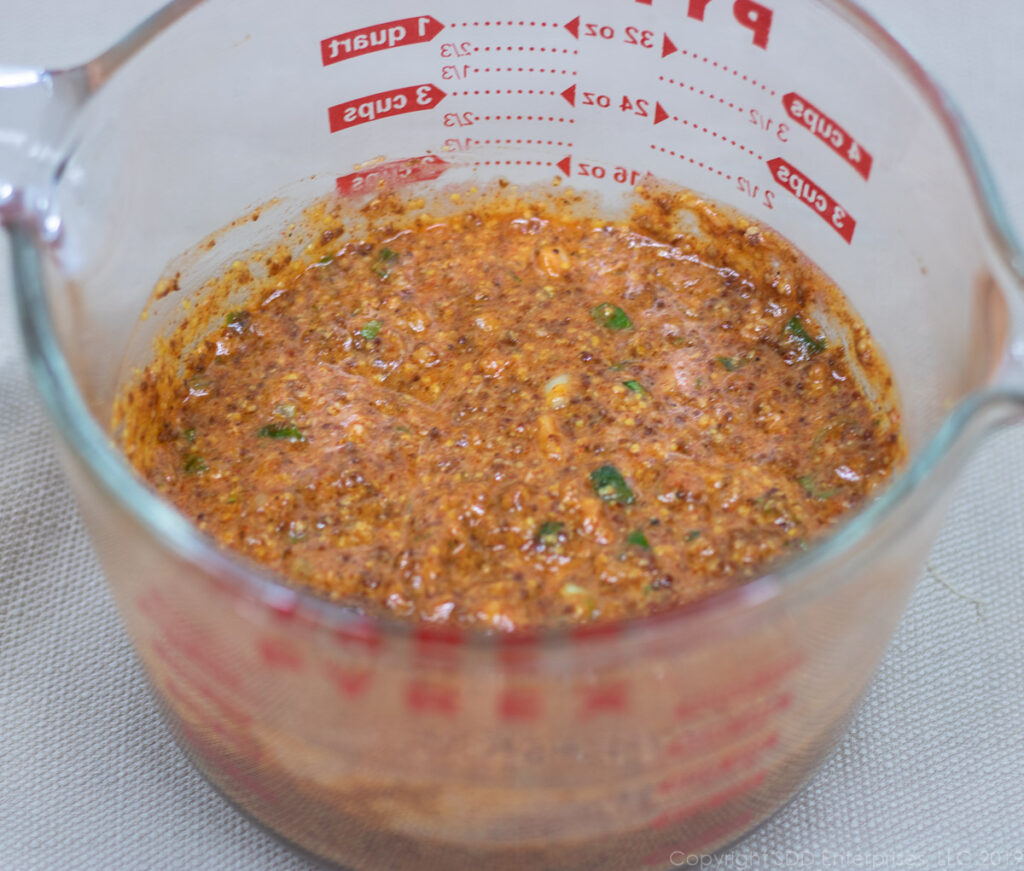 remoulade sauce ingredients mixed together in a large measuing cup
