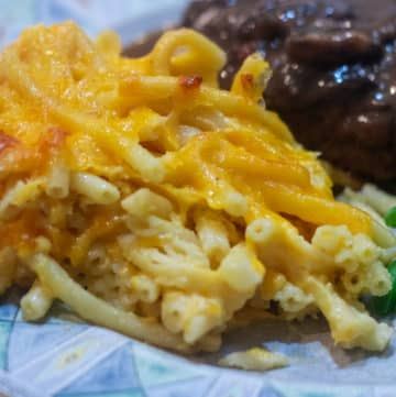macaroni and cheese on aplate with beef patty and green beans