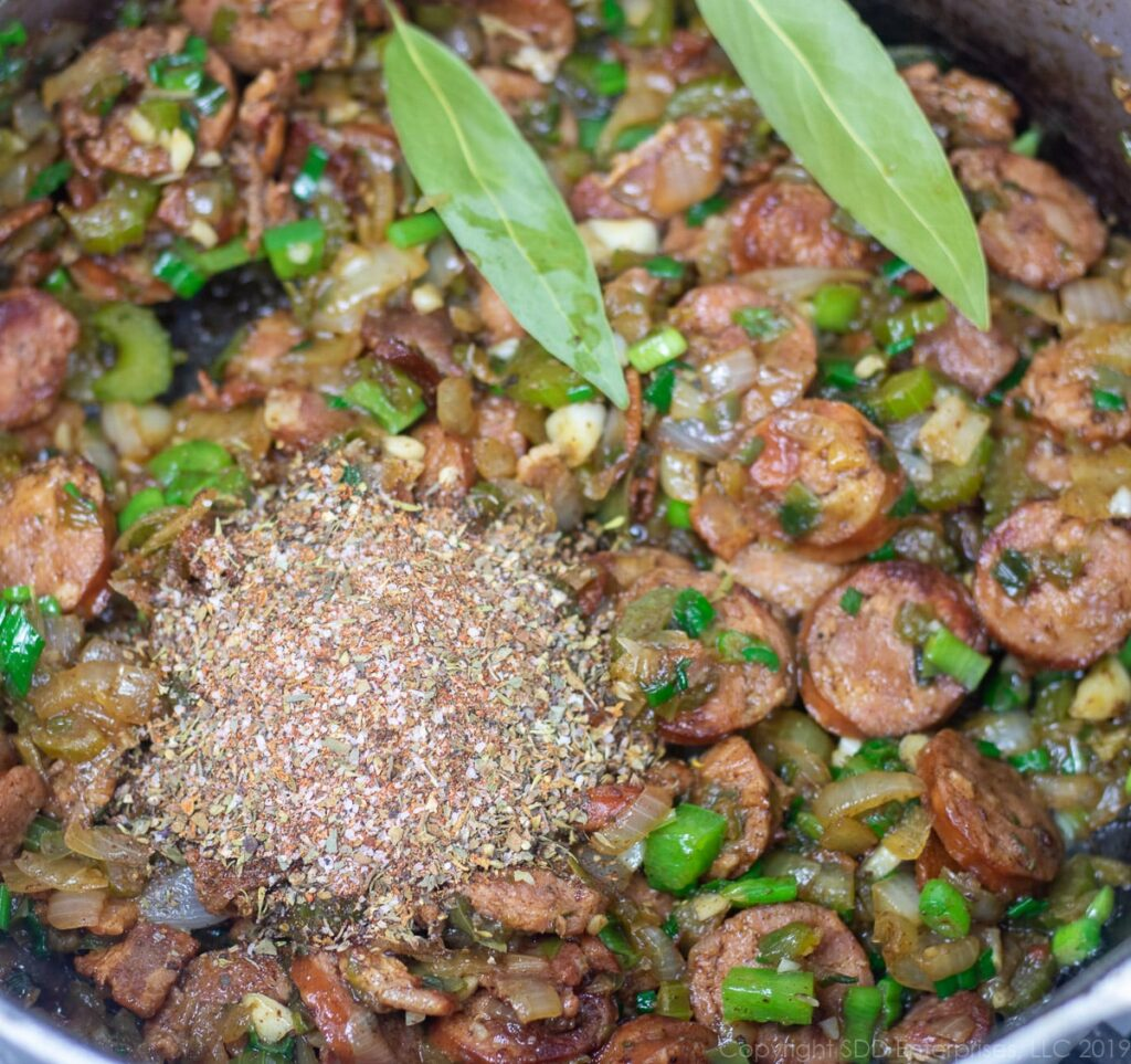 herbs and spices added to the vegetables and meats in dutch oven for creole jambalaya