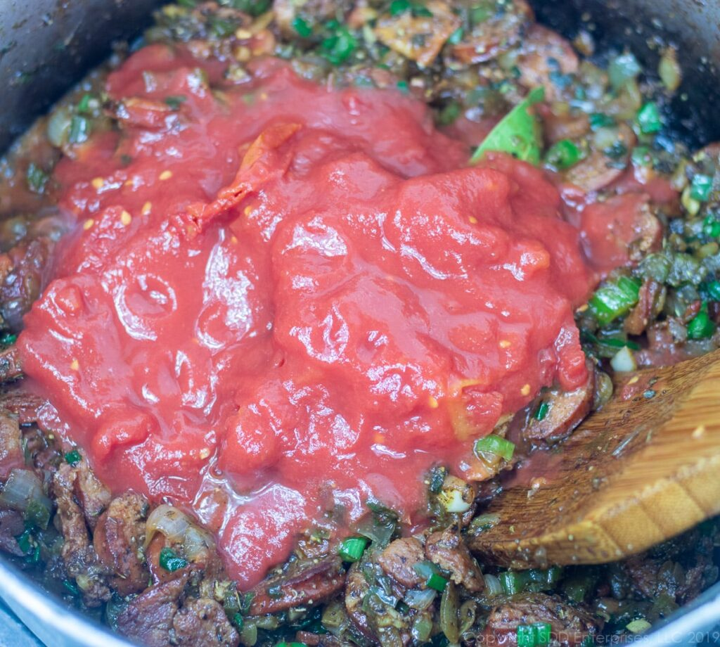 whole tomatoes added to the vegetables and meats in a dutch oven for creole jambalaya