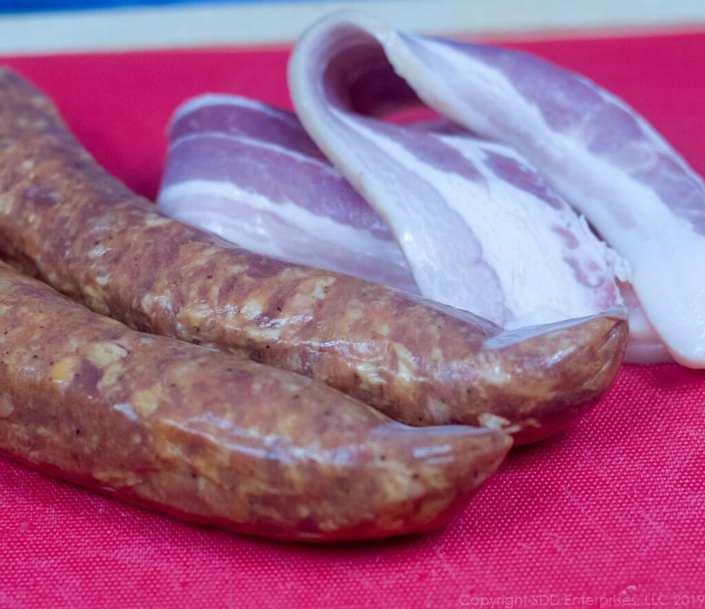 andouille sausage and bacon on a cutting board