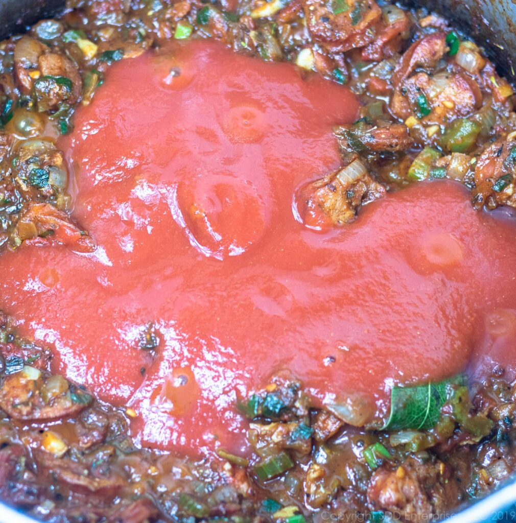 tomato sauce added to ingredients in dutch oven for creole jamabalaya