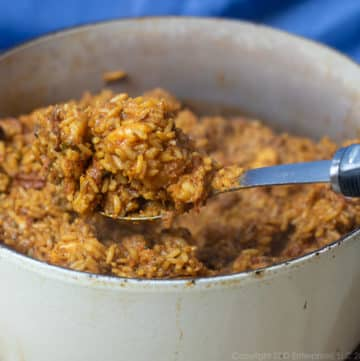 a spoonful of creole jambalaya held over a dutch oven of creole jambalaya