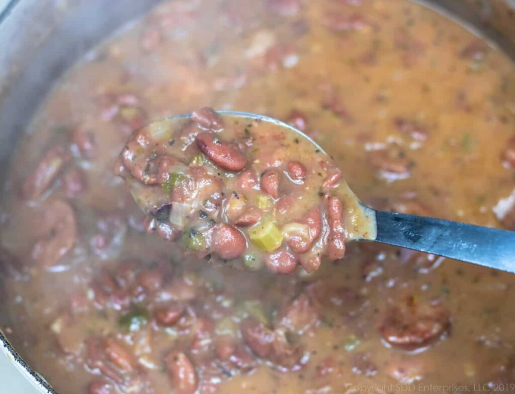 red beans and rice on a spoon over a dutch oven