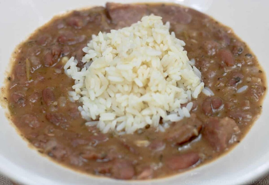 red beans with rice on top in a white bowl
