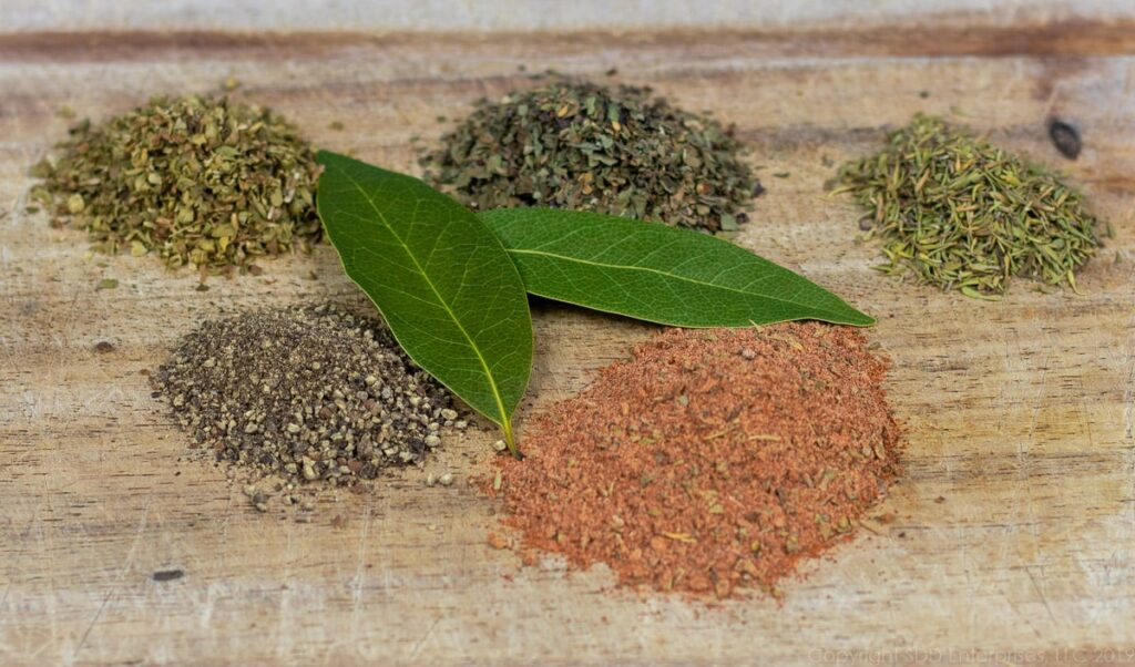 herbs and spices for red beans on a cutting board