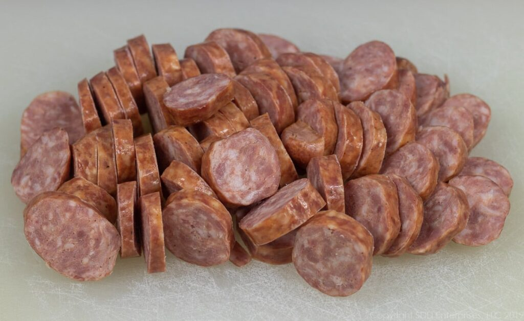 sliced smoked sausage on a cutting board for red bean