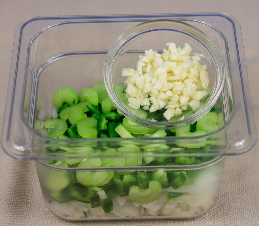 chopped yellow onions, bell peppers and celery in a clear container with a small bowl of chopped garlic on top