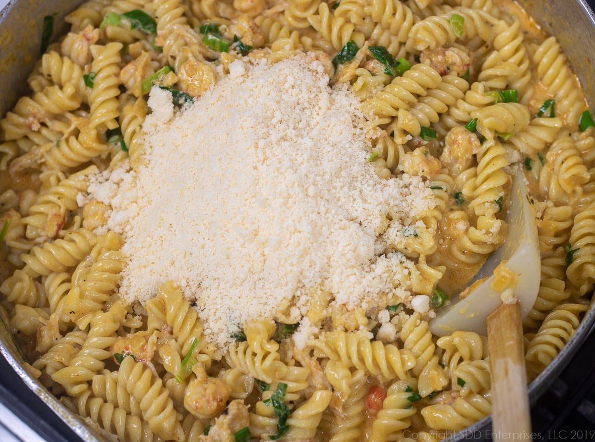 grated parmesan cheese added to the crawfish monica in a frying pan
