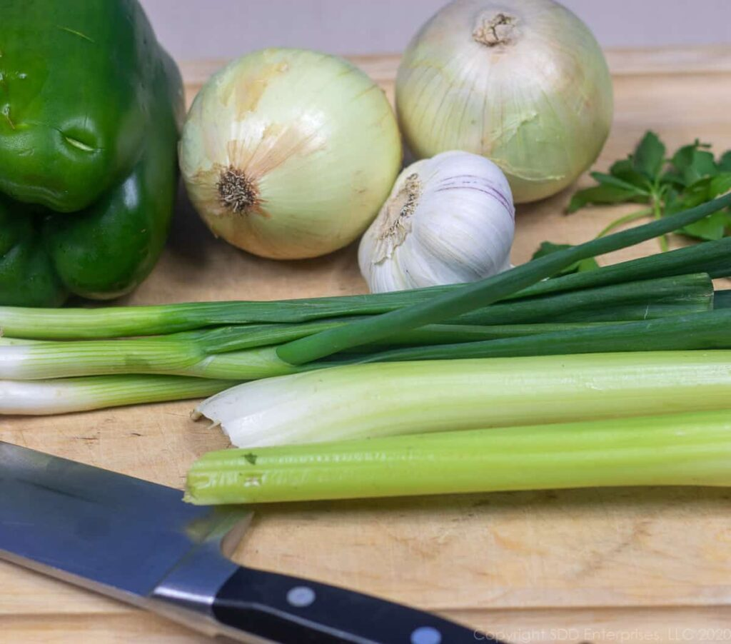 yellow onions, green onions, bell peppers, celery and garlic on a cutting board with a knife