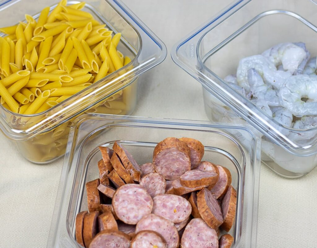 uncooked penne pasta, shrimp and sausage in seperate bowls