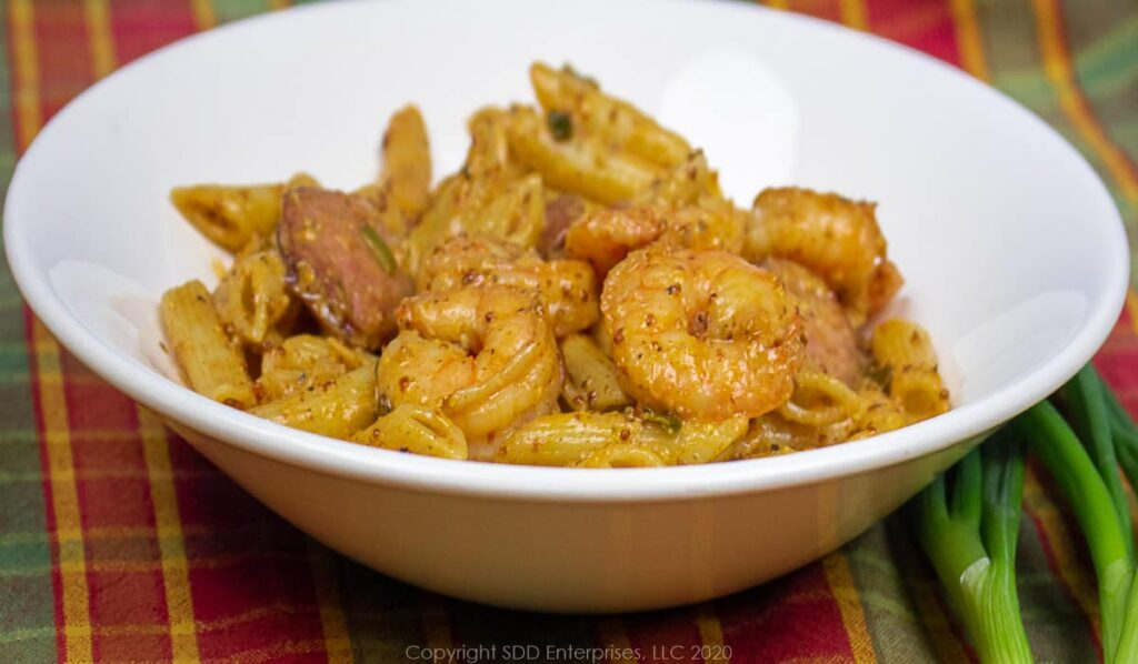 shrimp and sausage with pasta in sauce in a white bowl