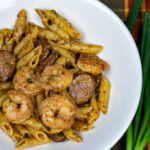 pasta with shrimp and sausage in a white bowl