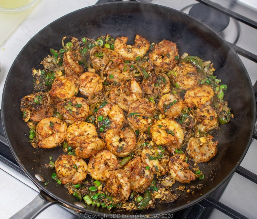 sauteeing shrimp with the onions and peppers in a skillet