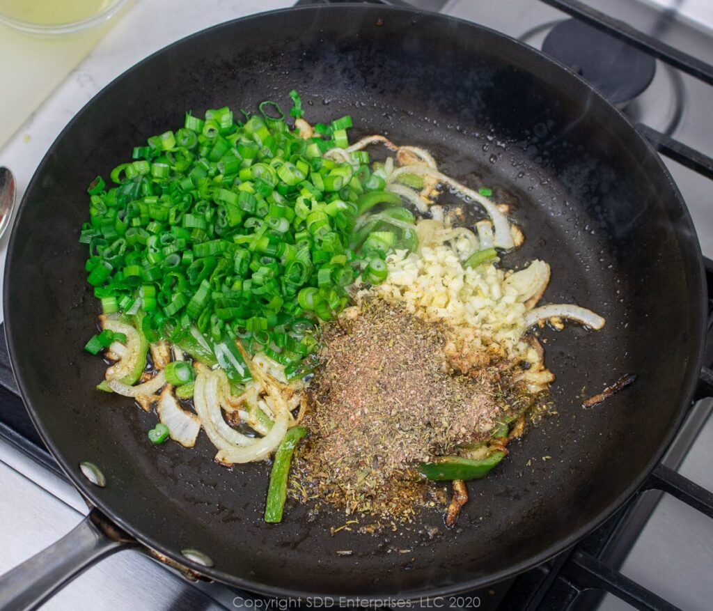 herbs, yellow onions and garlic added to onions and peppers in a skillet