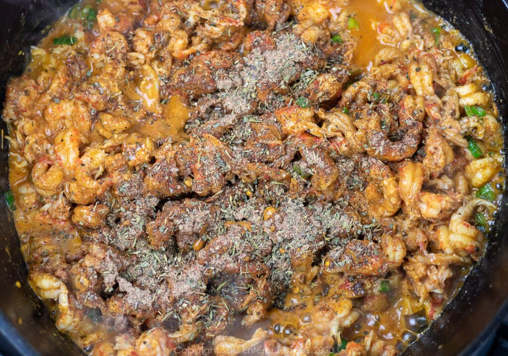 herbs and spices added to crawfish tails in a dutch oven