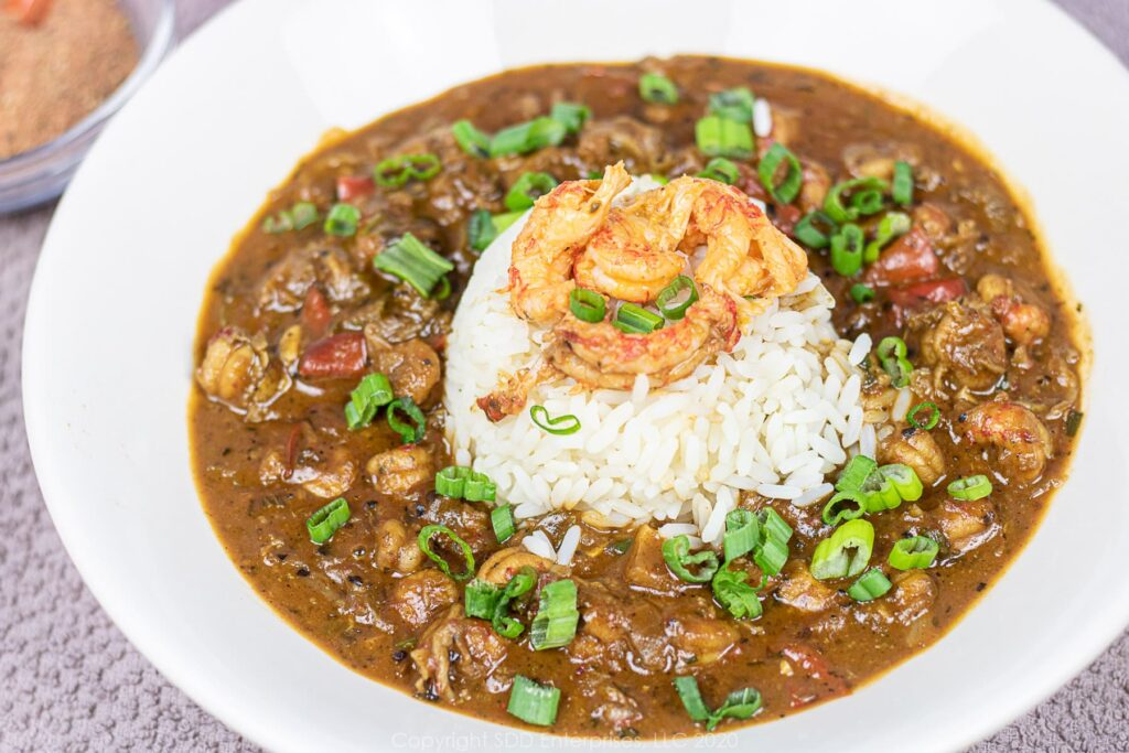 crawfish etouffee with rice and crawfish tails in a white bowl