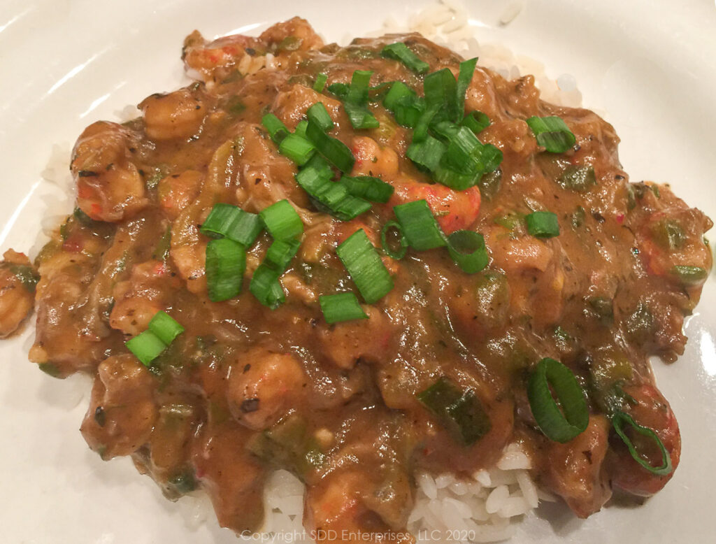 crawfish etouffee with garnish over white rice on a white plate