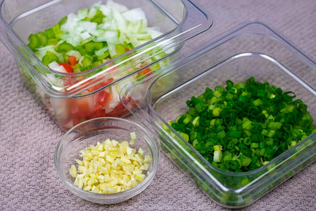 the trinity, chopped green onions and chopped garlic in prep bowls