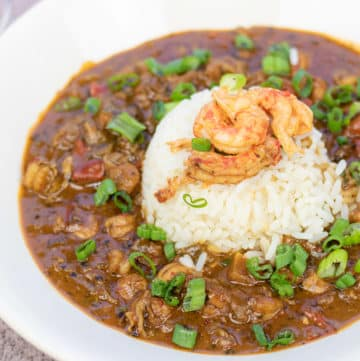 crawfish etouffee with a scoop of rice and crawfish tails on top in a white bowl