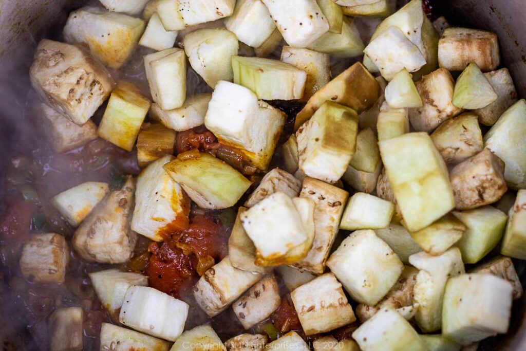 cubed eggplant added to sauteed vegetables for eggplant casserole