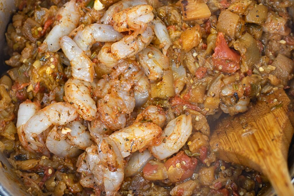 seasoned shrimp added to smothered eggplant for casserole in a dutch oven