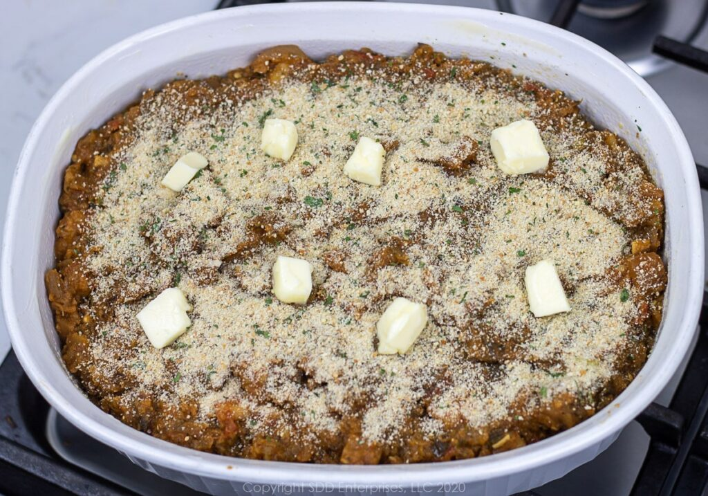 eggplant casserole in a baking dish with breadcrumbs and butter dots
