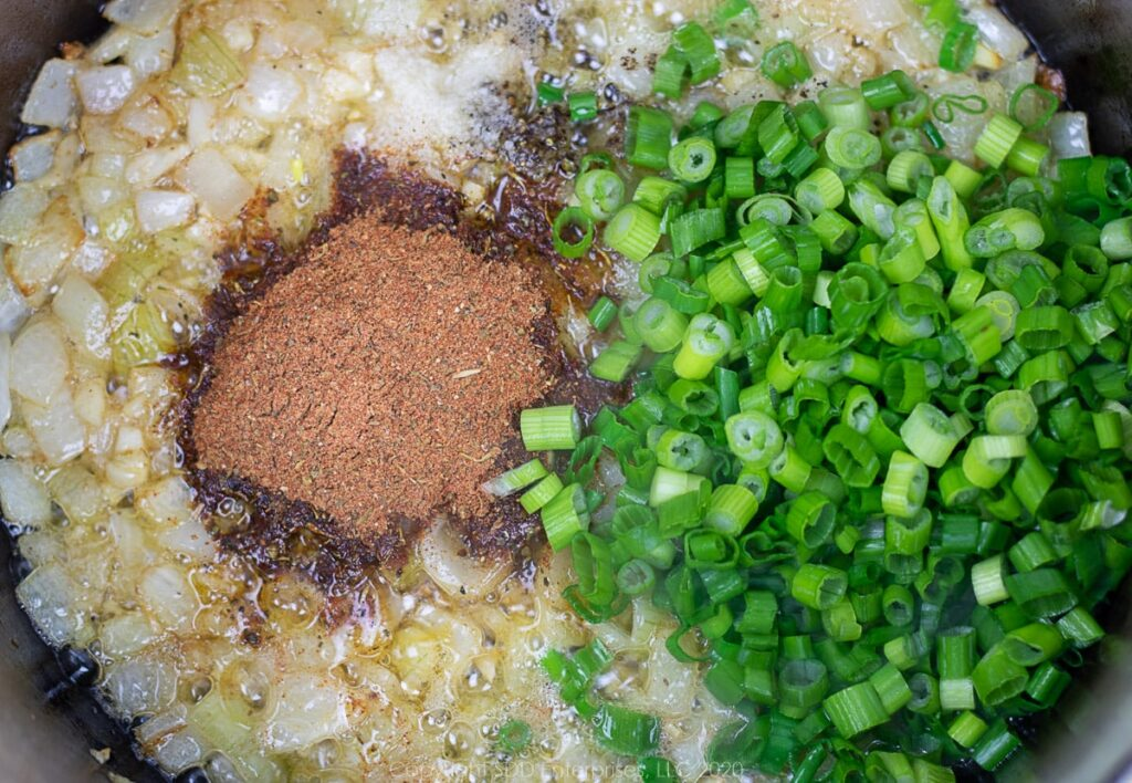 creole seasoning, green onions and salt and pepper added to sauteeing onions and garlic in a dutch oven