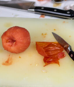a peeled tomato with skin and knife on a cutting board