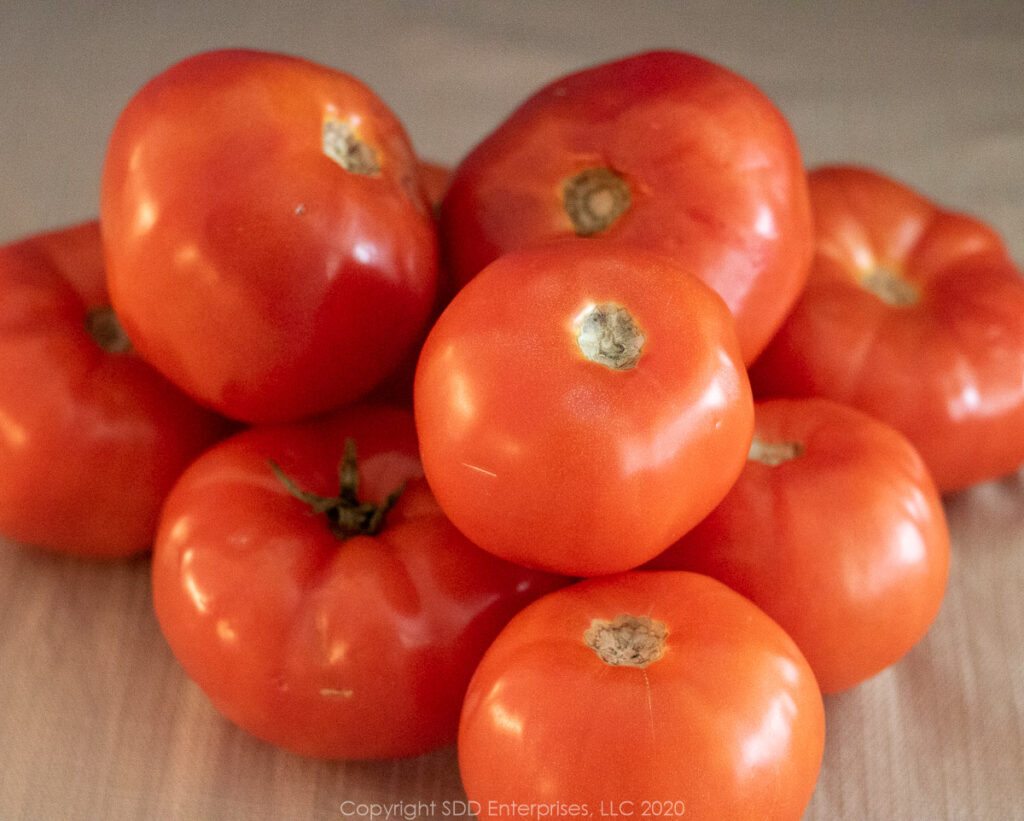 9 ripe tomatoes in a pile