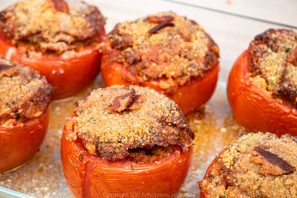 5 stuffed tomatoes with topping in a baking dish