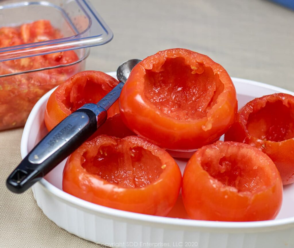 hollowed out tomatoes with a melon baller in a pyrex dish