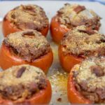 six stuffed tomatoes in a baking dish