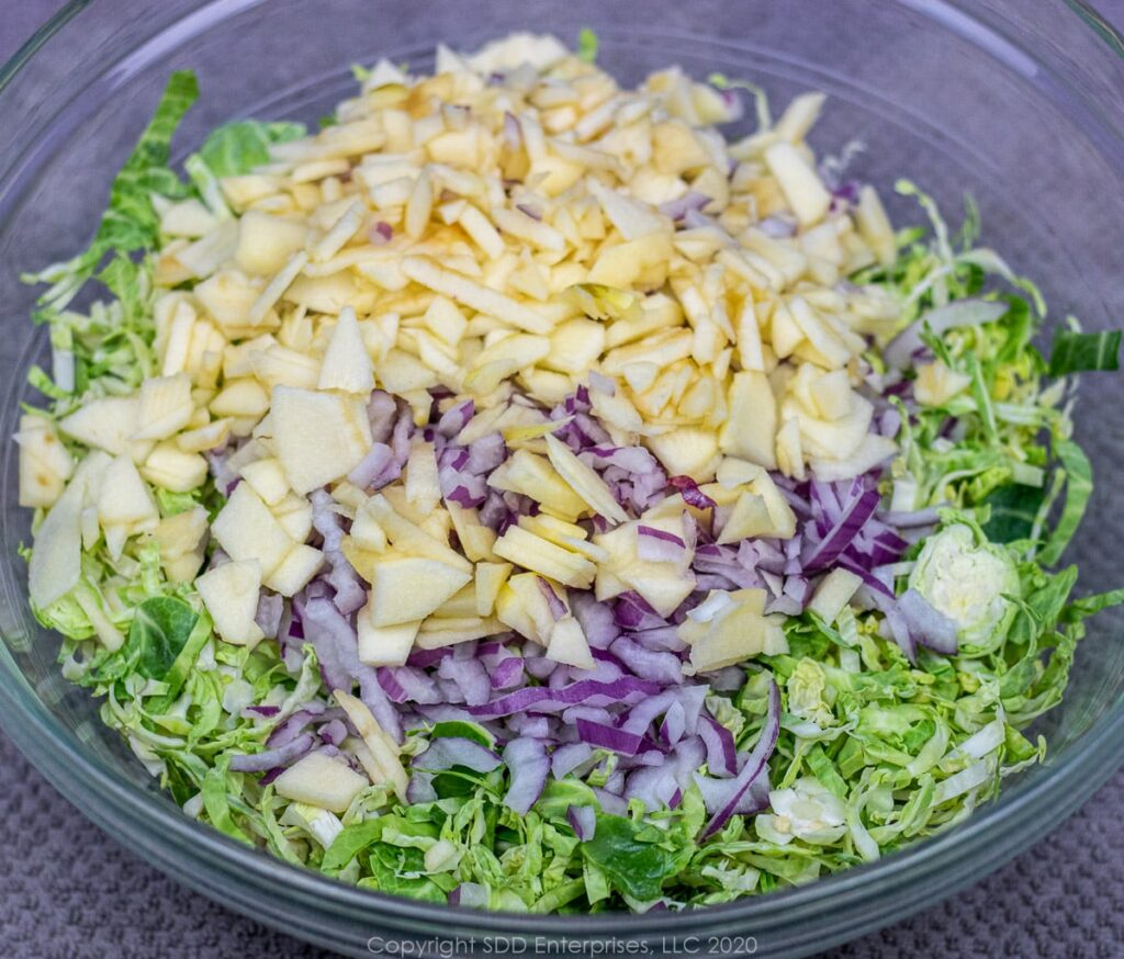 chopped ingredients for brussels sprout slaw in a mixing bowl