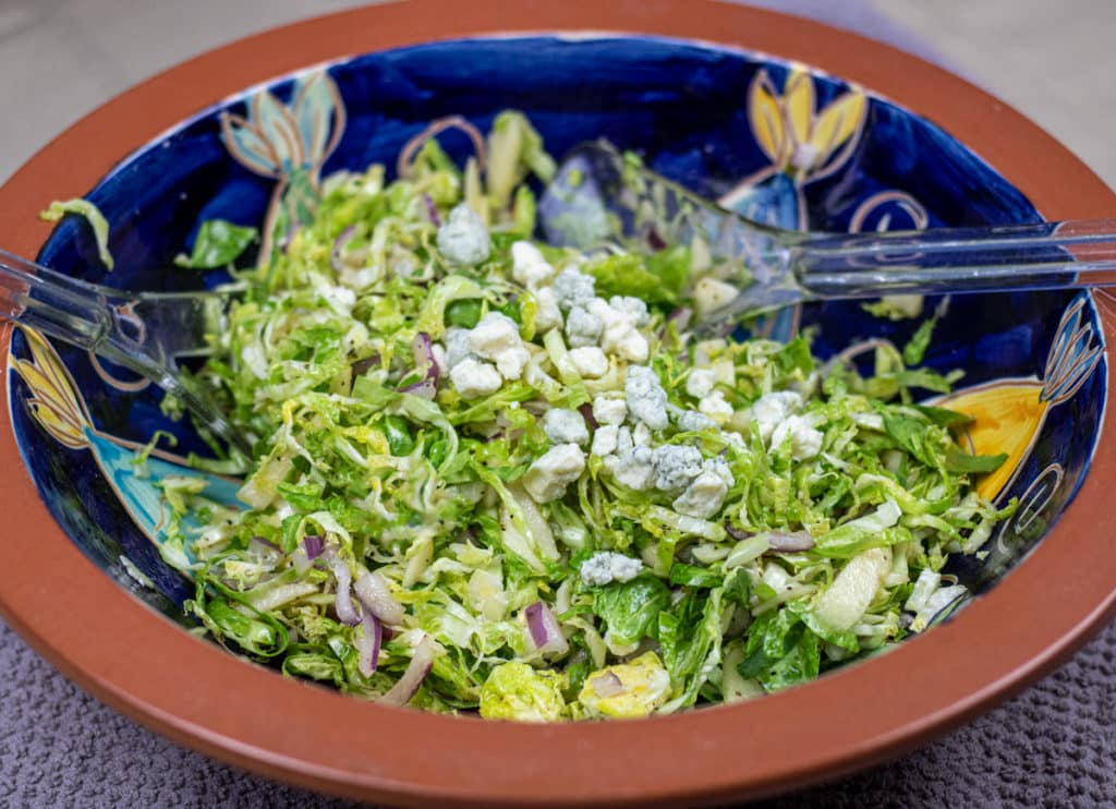 brussel sprout slaw with blue cheese garnish in a brown and blue bowl with salad tongs