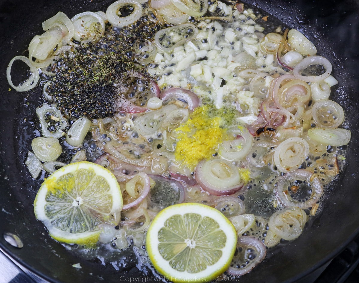herbs and spices, lemon zest, garlic and lemon peels added to sauteing shallots in a skillet