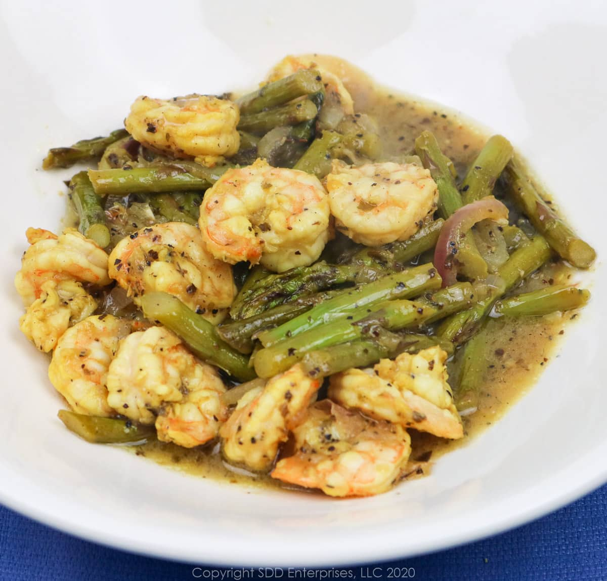sauteed shrimp and asparagus in a white bowl