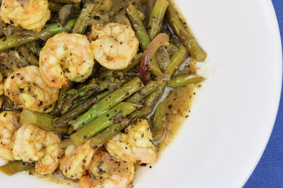 sauteed shrimp with asparagus in a white bowl