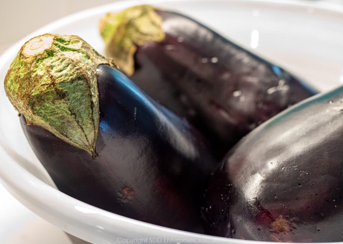 three purple eggplant in a white owl