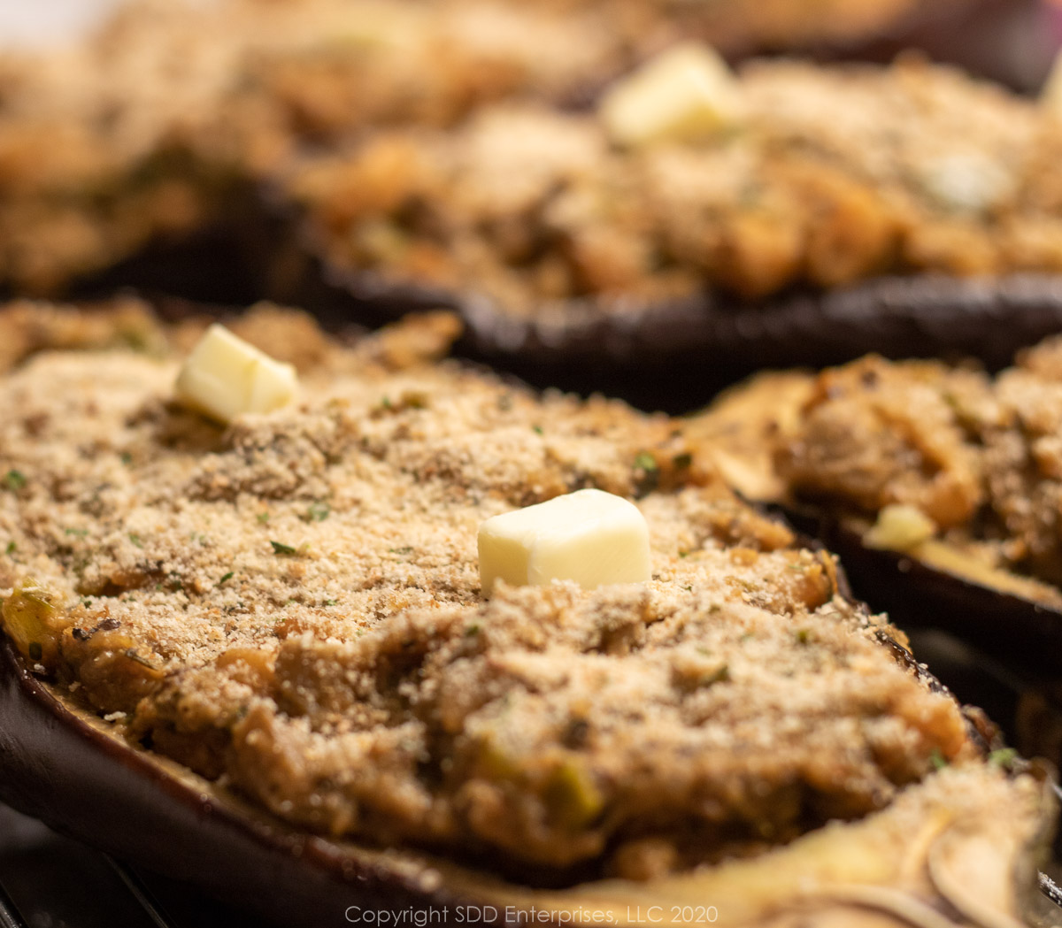 stuffed eggplant with breadcrumb topping and butter ready for the oven