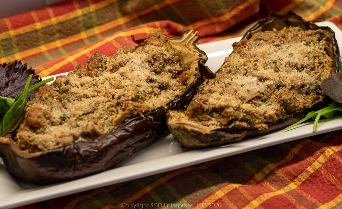 two roasted shrimp stuffed eggplant on a white platter and a cloth background