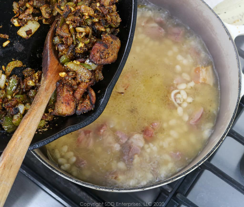 adding sauteed vegetables into simmering navy beans in a dutch oven